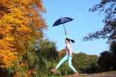 Sweet girl jumping with umbrella in autumnal park — Stock Photo