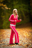 Blonde girl young woman running jogging in autumn fall forest park — Stock Photo