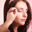 Stock Photo: Makeup artist stylist applying eyeshadow on eyelid of woman