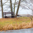Rural. Single wooden bench on river bank or lake shore outdoor — Stock Photo