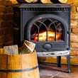 Fireplace with fire flame and firewood in barrel interior. Heating. — Stock Photo #41972623