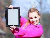Woman teenage girl in pink tracksuit showing blank tablet outdoor — Stock Photo