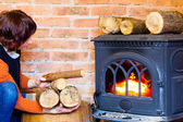 Woman putting some more wood on fireplace. Heating. — Стоковое фото