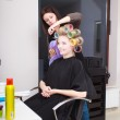Woman in beauty salon. Blond girl with hair curlers rollers by hairdresser. Hairstyle. — Stock Photo
