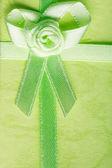 Giftbox closeup. Ribbon with bow on green background — Stock Photo