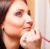 Makeup artist applying with pencil cosmetic on lips of woman — Stock Photo