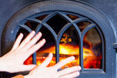 Woman warming her hands at fire fireplace interior. Heating. — Photo