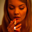 Young woman with lighter lighting up cigarette. Girl smoking. — Stock Photo
