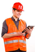 Mężczyzna robotnik w kamizelka ratunkowa i kask za pomocą tabletu — Zdjęcie stockowe