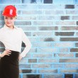 Female engineer woman architect in red safety helmet and brick wall — Stock Photo
