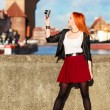 Fashionable tourist girl taking picture with camera old town Gdansk — Stock Photo