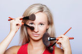 Beauty procedures, woman holds make-up brushes near face. — Stock Photo