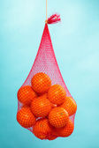 Fresh oranges fruits in mesh from supermarket — Zdjęcie stockowe