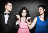 Two elegant women with gun gangster in handcuffs — Stock Photo