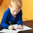 Blond boy child kid with pen writing on piece of paper. At home. — Stock Photo #42984397