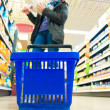 Woman shopping with blue basket at supermarket shop. Retail. — Stock Photo