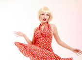 Beautiful pinup girl in blond wig and retro red dress dancing. Party. — Стоковое фото