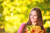Fall season. Portrait girl woman with bunch of autumnal leaves — 图库照片