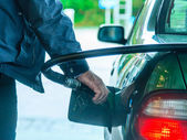 Car refuel fueling at the filling station, holding a fuel pump — Stock Photo