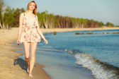 Summer vacation. Girl walking alone on the beach. — Stockfoto