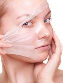 Girl woman in facial peel off mask. Skin care. — Stockfoto
