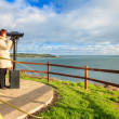 Woman looking through sightseeing binoculars overlooking the ocean — Stock Photo #43338649