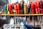 Assortment of tools hanging on wall. Screwdrivers in mechanic garage car service — Stock Photo