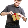 Holiday. Man got golden gift box with red ribbon — Stock Photo #43580425