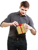 Holiday. Man got golden gift box with red ribbon — Stock Photo