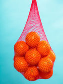 Fresh oranges fruits in mesh from supermarket — Stock fotografie