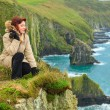 Woman sitting on rock cliff looking to ocean Co. Cork Ireland — Stock Photo #43649543