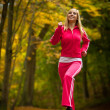 Fitness fit woman blond girl doing exercise in autumnal park. Sport. — Stock Photo #43649695