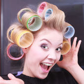 Cheerful funny blond girl hair curlers rollers by haidresser in beauty salon — Stock Photo