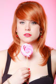 Sexy young woman holding candy. Redhair girl eating sweet lollipop — Stock Photo