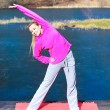 Woman teenage girl in tracksuit doing exercise on pier outdoor — Stock Photo #43713005