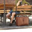 Young handsome man with suitcase waits on bench — Stock Photo #43713569
