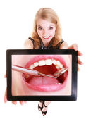 Girl showing white teeth on tablet. Dental care. — Stockfoto