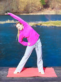 Woman teenage girl in tracksuit doing exercise on pier outdoor — Stock Photo