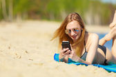 Summer vacation Girl with phone tanning on beach — Stok fotoğraf