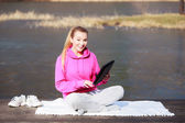 Woman teenage girl in tracksuit using tablet on pier outdoor — Stock Photo