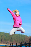 Cheerful woman teenage girl in tracksuit jumping showing outdoor — Stock Photo