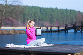 Woman teenage girl in tracksuit showing tablet on pier outdoor — Stock Photo