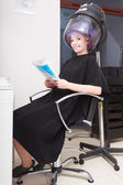 Woman client curlers  in hair reads magazine hairdressing beauty salon. — Stock Photo