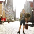 Young handsome man with suitcase on street — Stock Photo