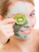 覆盖用猕猴桃一只眼睛的脸上的泥面膜的女人 — 图库照片