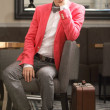 Young handsome stylish man with suitcase waits — Stock Photo #44634947
