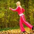 Blonde girl young woman running jogging in autumn fall forest park — Stock Photo #44634999