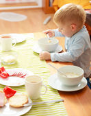 Boy kid child eating corn flakes breakfast morning meal at home. — Stock Photo