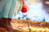 Girl relaxing in the autumn park enjoying hot drink — Stock Photo