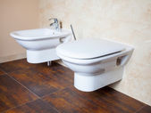 Hygiene. White porcelain bidet and toilet. Interior of bathroom. — Stock Photo